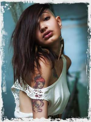 Vagma evokes a sultry and daring muse as she bares her slender physique with tattoos and poses erotically in front of the camera.